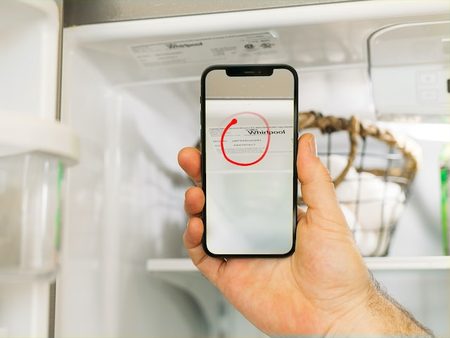 A customer holds their iPhone up to a label in a fridge and the expert uses Streem's Marker tool to indicate where to look.