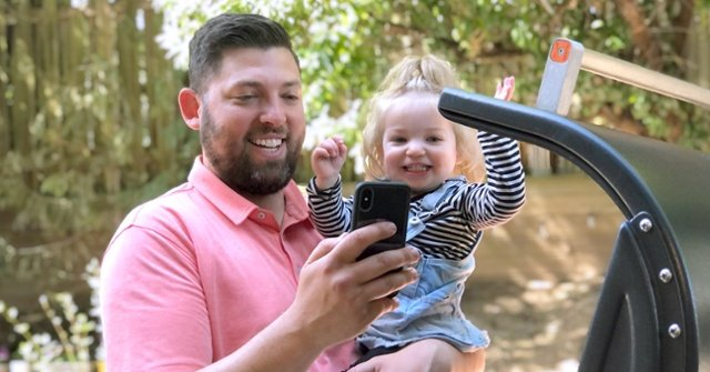 A man and his daughter use live video support to talk to customer service about their grill.